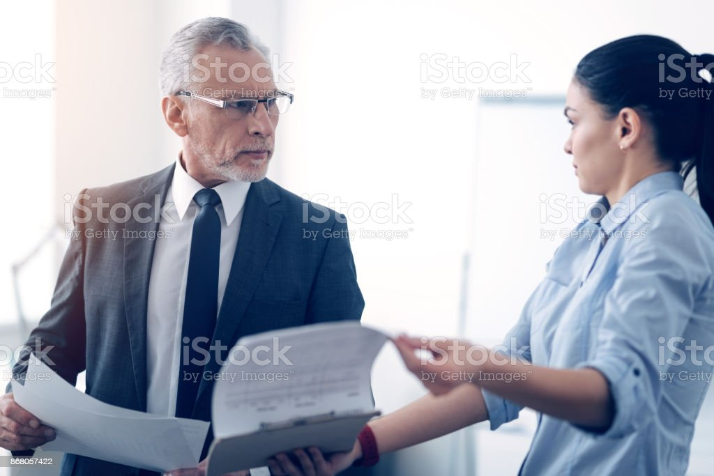 Grumpy chief and his female office worker arguing over documents stock photo