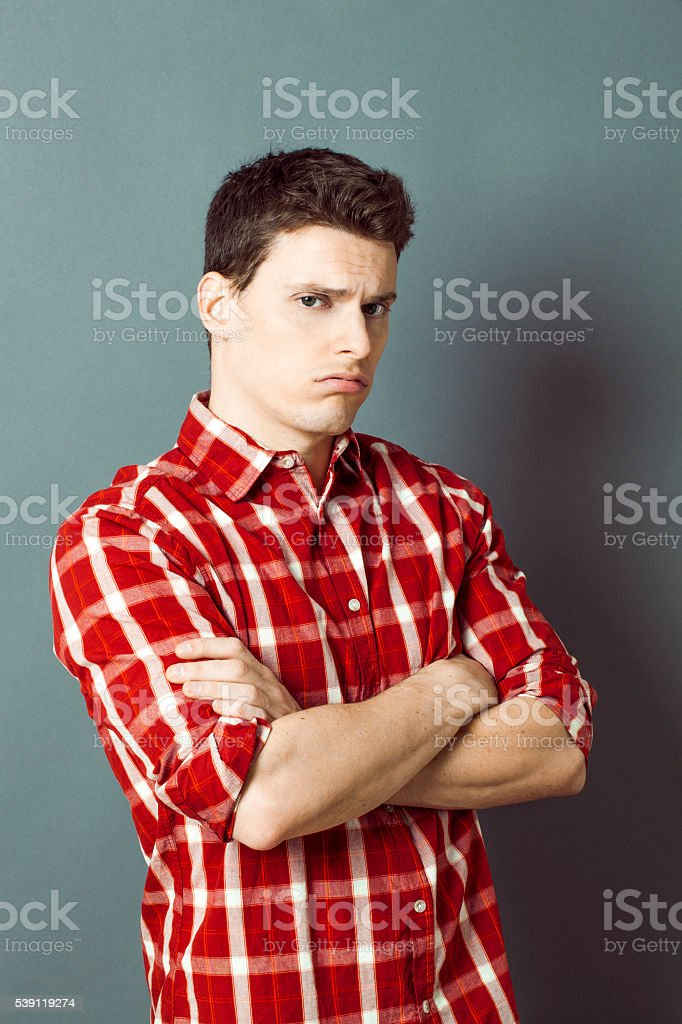 grumpy depressed young sportsman crossing his arms for boredom stock photo