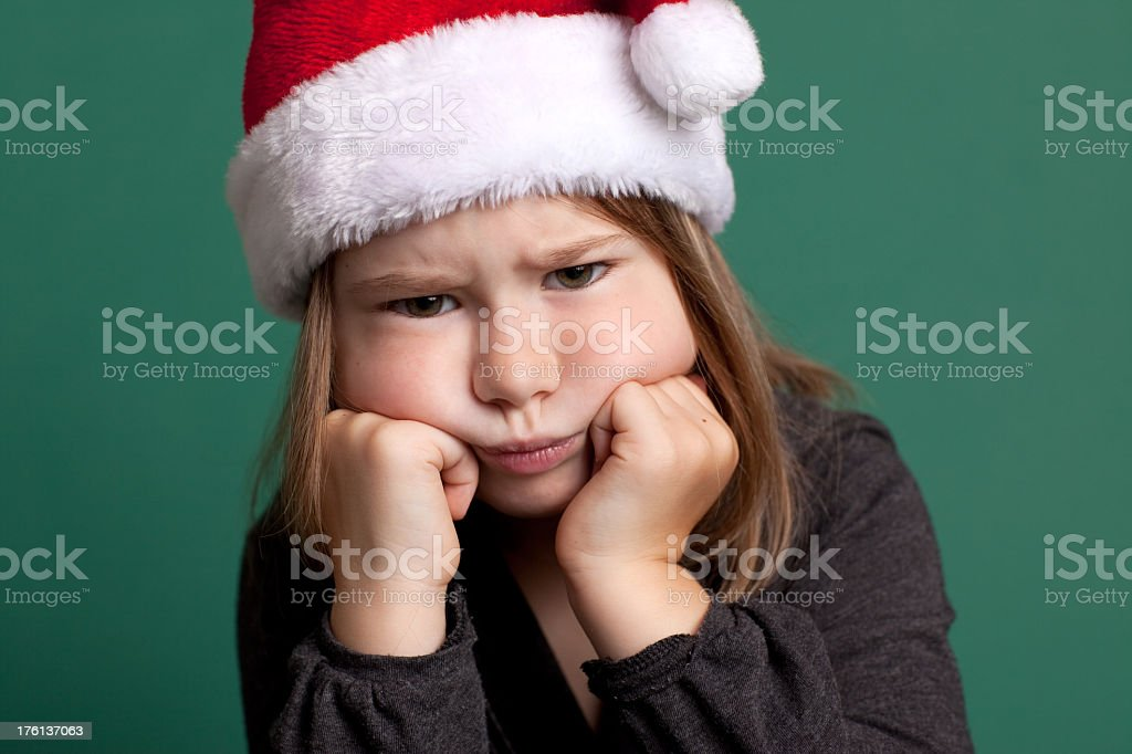Grumpy Little Girl Wearing Santa Hat royalty-free stock photo