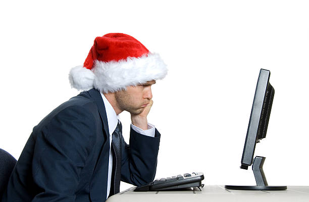 Grumpy office worker at his desk with a Santa hat stock photo