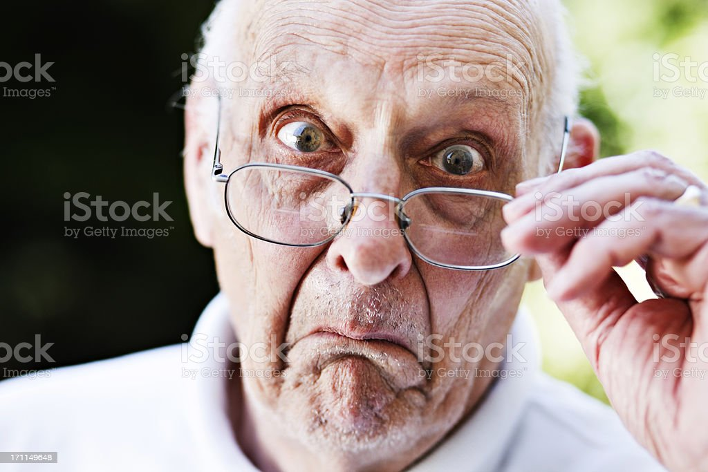 Grumpy old man looks over spectacles, shocked and disapproving stock photo