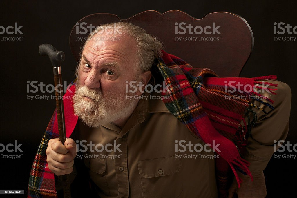 Grumpy old man shakes his cane and frowns stock photo