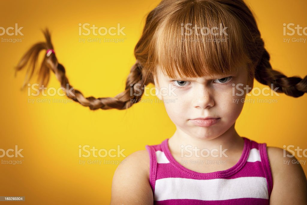 Grumpy Red-Haired Girl with Upward Braids and a Scowl royalty-free stock photo