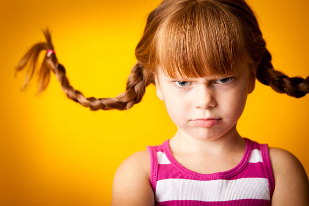 Grumpy Red-Haired Girl with Upward Braids and a Scowl stock photo