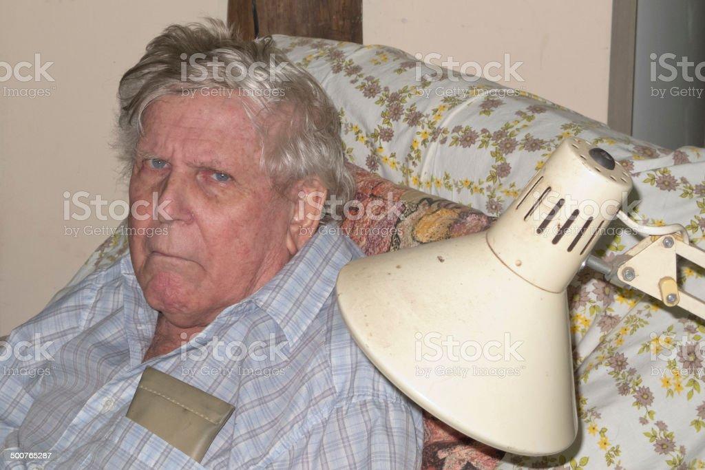 Grumpy Senior Man sitting on a comfy chair stock photo