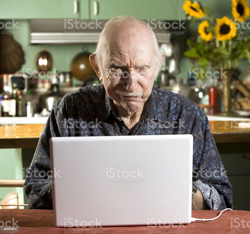 Grumpy Senior Man with a Laptop Computer stock photo