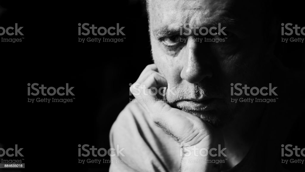Grumpy serious man with chin leaning on hand. stock photo