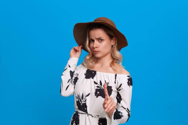 grumpy junges modell mit lockigen blonden haaren in einem sonnenuntergang hut und weißes kleid wedelt finger stehend auf einem blauen hintergrund. - spielerfrauen stock-fotos und bilder