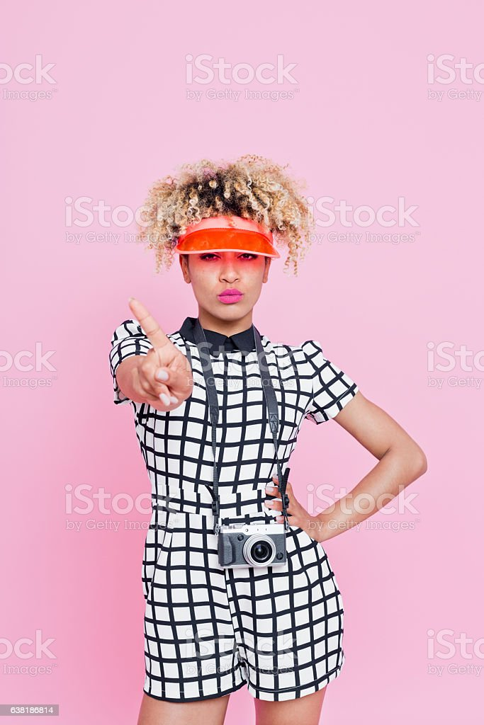 Grumpy young tourist woman showing stop hand gesture Closeup portrait of grumpy or annoyed young afro american woman with dyed hair, wearing grid check playsuit and sunshade cap with a small camera on here neck, She is looking at the camera with sad or unhappy expression and showing stop hand gesture. Standing against pink background 25-29 Years Stock Photo
