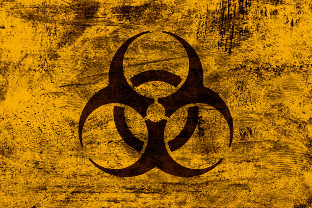 Grunge biohazard sign on yellow-orange grunge background A black biohazard symbol is superimposed on yellow-orange grunge background. Layer effect and color management made with Photoshop. decontamination stock pictures, royalty-free photos & images