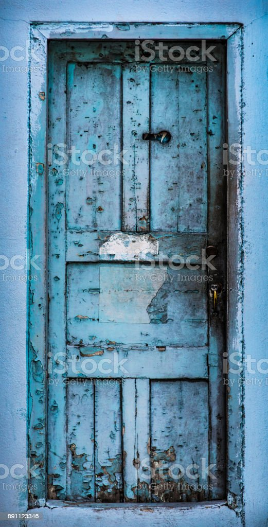 Grunge blue door with stains, chipped paint and rough and dirty texture stock photo