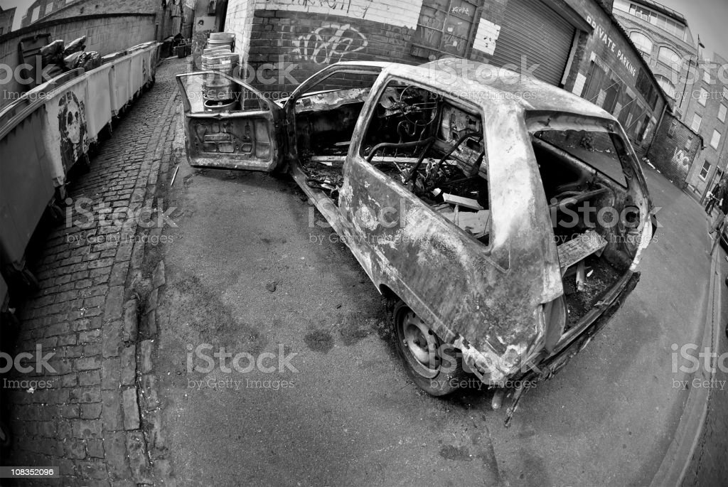 Grunge burnt car in the street - Black and white royalty-free stock photo