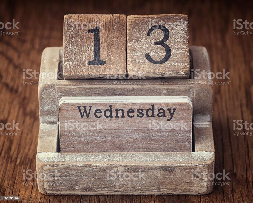 Grunge calendar showing Wednesday the thirteenth on wood backgro stock photo
