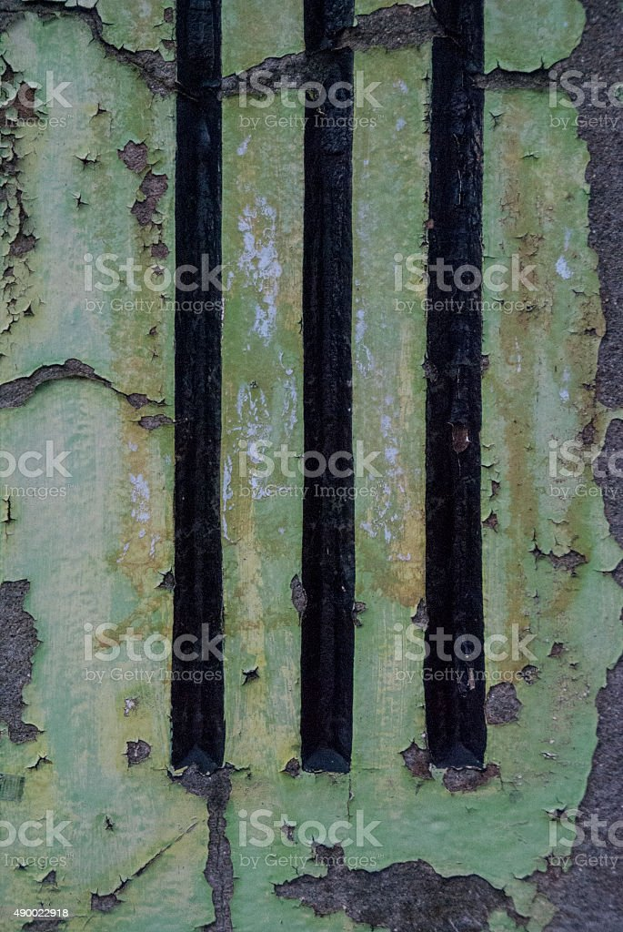 Vintage grunge concrete ventilation grill with flaking green paint...