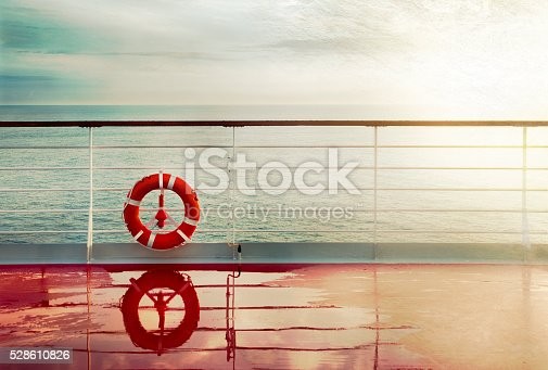 Grunge cruise deck background at dawn.Lifebuoy hand railing deck. Vintage look.