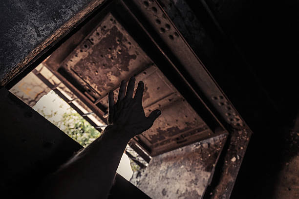 Grunge dark interior with open rusted door and male hand stock photo