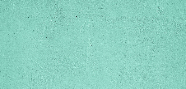 Empty Grunge Decorative Light Green plaster Wall Texture. Abstract Painted Wall Surface. Wide Angle Rough Background or Web Banner With Copy Space For design