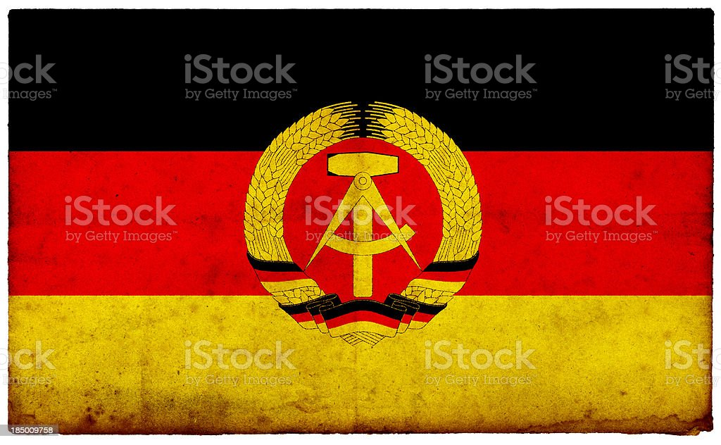 Grunge Former East German Flag on rough edged old postcard stock photo