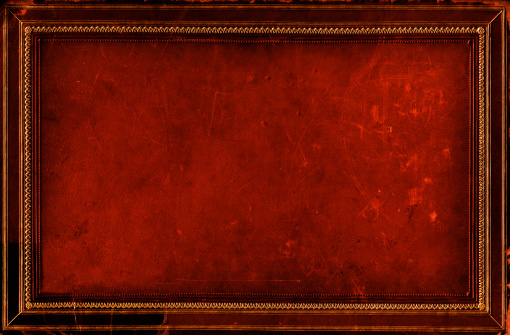 A grungy dirty background. The damaged leather with gold gilt border.