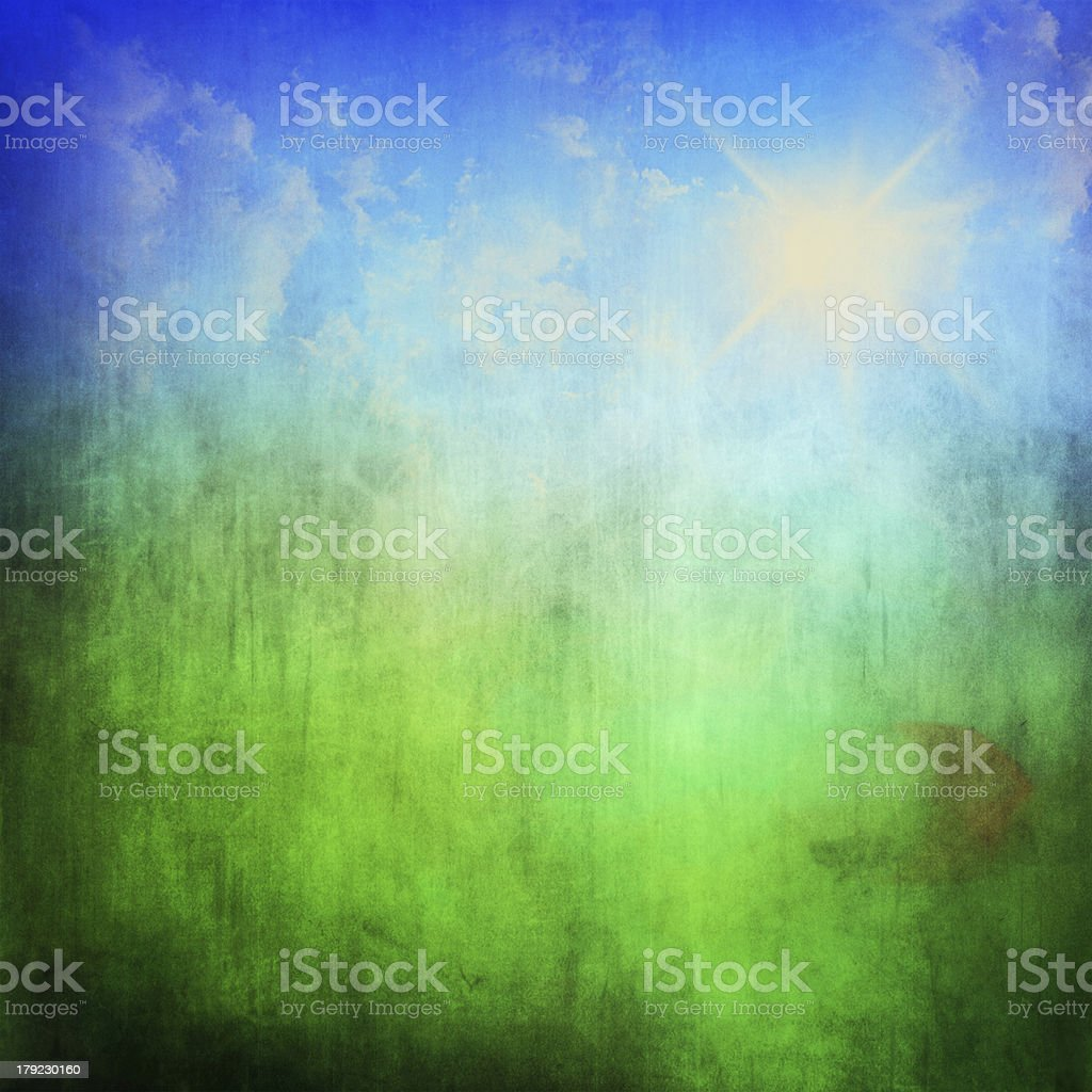 Grunge green field and blue sky stock photo