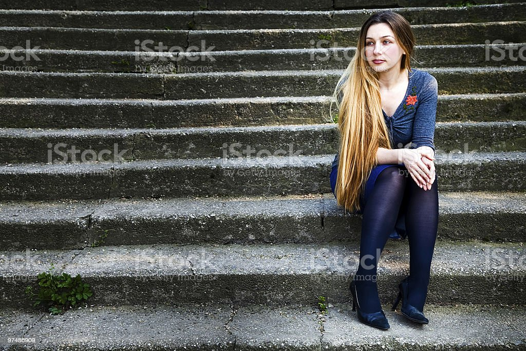Grunge portrait of pensive beautiful woman on steps royalty-free stock photo
