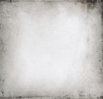 A close-up, cropped image of a light gray cement or plaster wall with an irregular surface of mounds and cracks that has black mold or paint spatters and smudges along the outer edge of the image.  The cracks appear subtly black and gray, embedded with black mold or paint.  The image is lighter in the middle, with a broad grey border that grows darker toward the edges, making the image appear raised in the middle and sloping toward the sides.  There is abundant space for text to be superimposed over the section of wall.