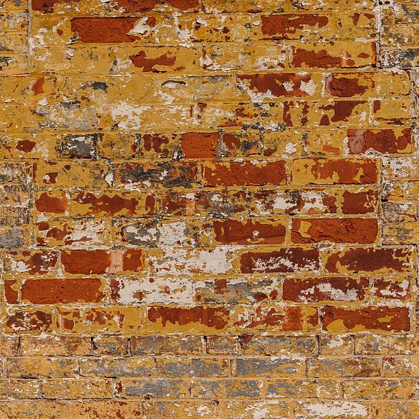 Grunge weathered brick red yellow brick wall peeling paint stock photo