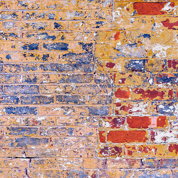 Grunge weathered red yellow brick wall peeling paint stock photo
