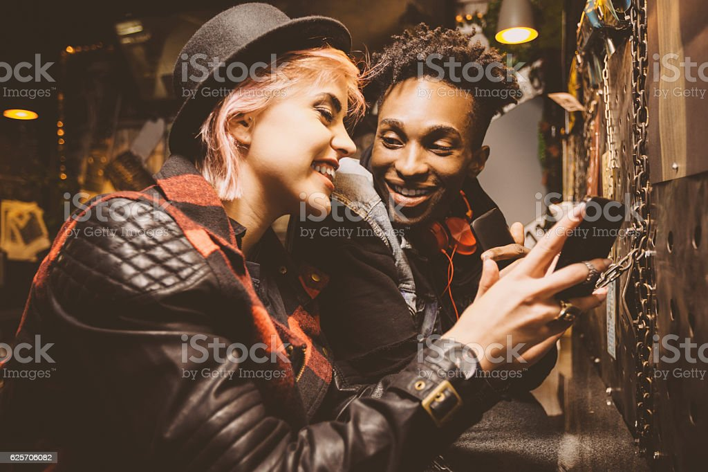 Grunge young couple in a pub, girl using smart phone stock photo