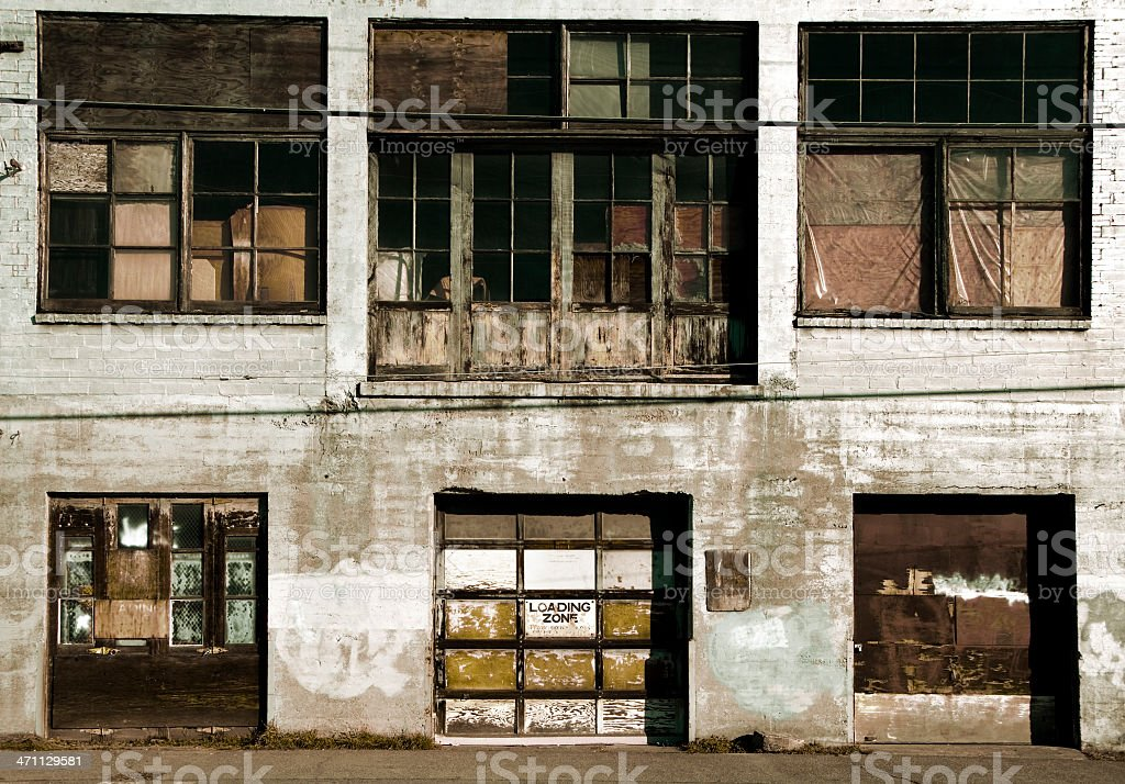 Grungy alley with broken windows and 'Loading Zone' sign royalty-free stock photo