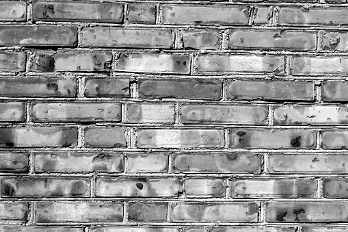 973649382 istock photo Grungy black and white brick house wall. 615634282