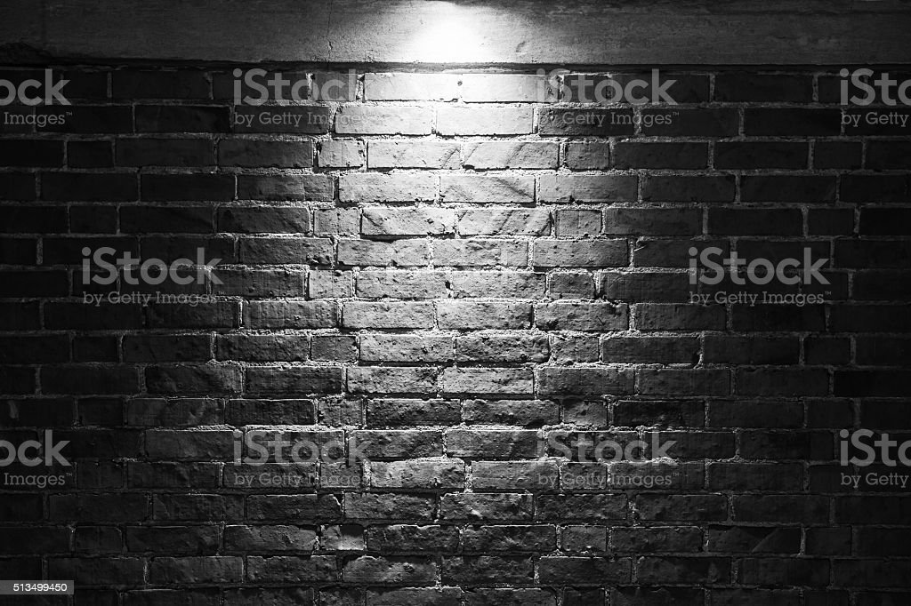 Grungy dark brick wall with spotlight stock photo