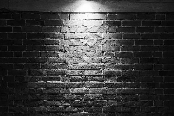 Grungy dark brick wall with spotlight stock photo