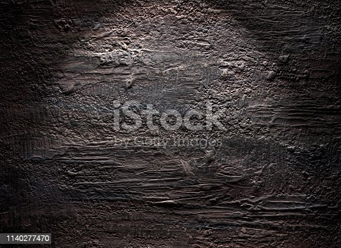 Grungy dark stucco wall with spotlight, background photo texture