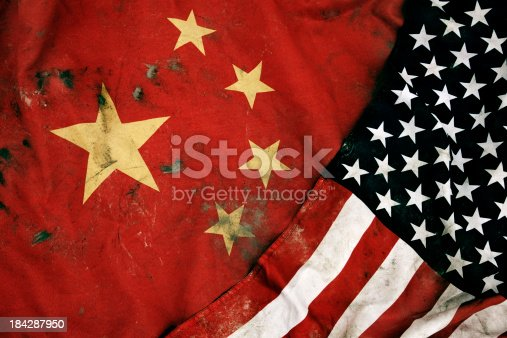 Low key photography of grungy old flags of China and USA.