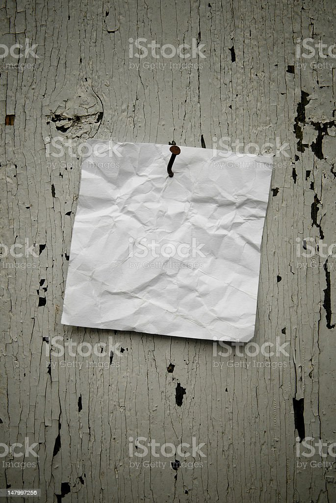 Grungy note paper nailed on weathered background. royalty-free stock photo