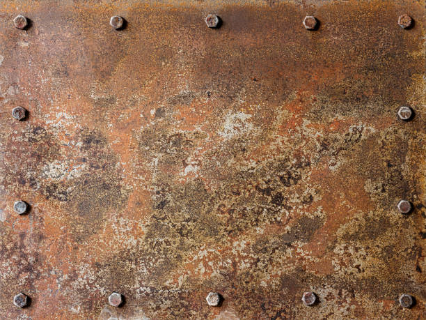Grungy old multi-colored rusted and patina covered abstract metal plate background with bolts surrounding the plate on the edges, lots of eroded character. stock photo