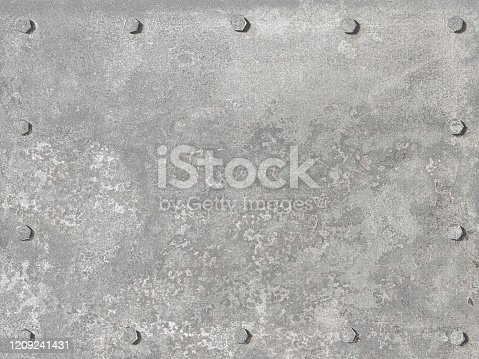 An old pitted and weathered gray metal sheet background framed by old rusty bolts. Lots of texture.