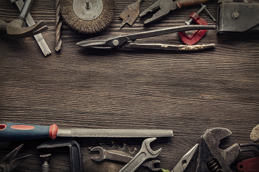 grungy old tools on a wooden background