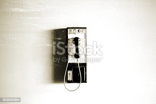 A grungy image of a pay phone and shadow on a blank white wall.