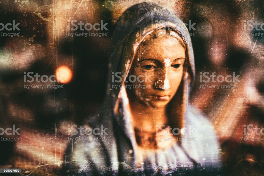 Grungy processing of an old and chipped plaster bust of Virgin Mary, one of the iconic figures of some Christian religion. stock photo