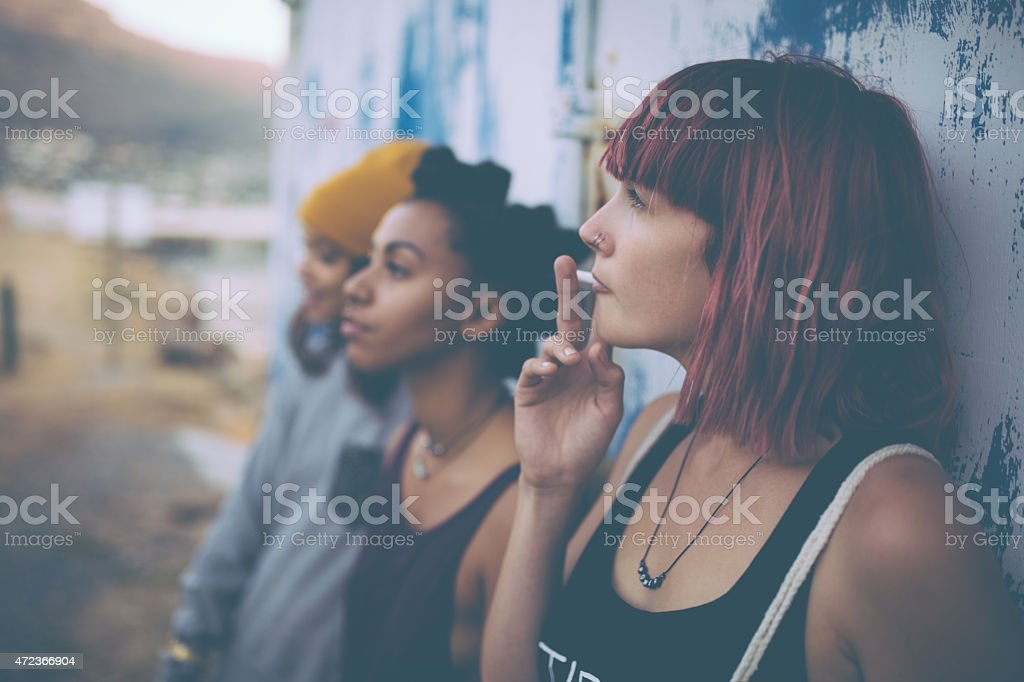 Grungy teen with pink hair hanging out smoking with friends stock photo