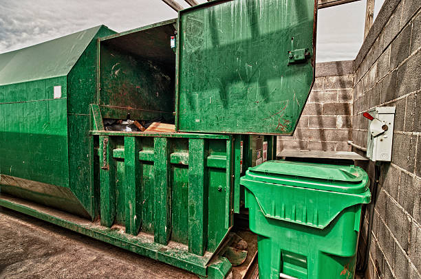 Grungy Trash Dumpster With Compactor The business end of an industrial garbage bin with attached compactor. HDR image. compactor stock pictures, royalty-free photos & images
