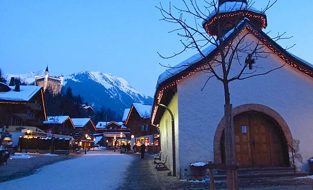 Gstaad Switzerland winter shoppers on snowy street at twilight stock photo