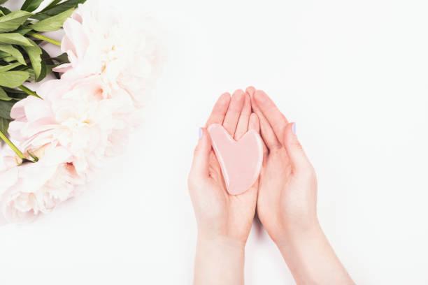 Gua sha Massage Jade Werkzeug in Frauenhänden. – Foto