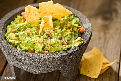 A high angle close up of creamy guacamole in a Mexican molcajete and crunchy corn chips. Shot on an old wooden outdoors table with deliberated copy space on upper right side.