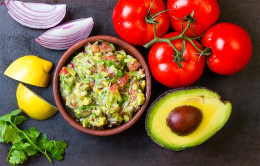 Guacamole and ingredients - avocado, tomatoes, onion, cilantro dark background.