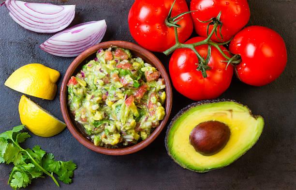 guacamole e ingredientes de abacate, tomate, cebola, coentro fundo escuro. - guacamole - fotografias e filmes do acervo