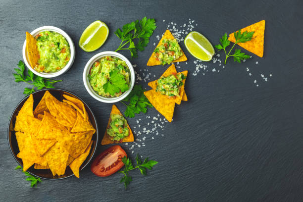 Guacamole and nachos with ingredients on the background of a black stone board stock photo