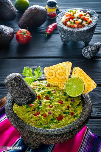 Guacamole avocado Mexican recipe in stone molcajete with ingredients tortilla chips and pico de gallo sauce on black wood background